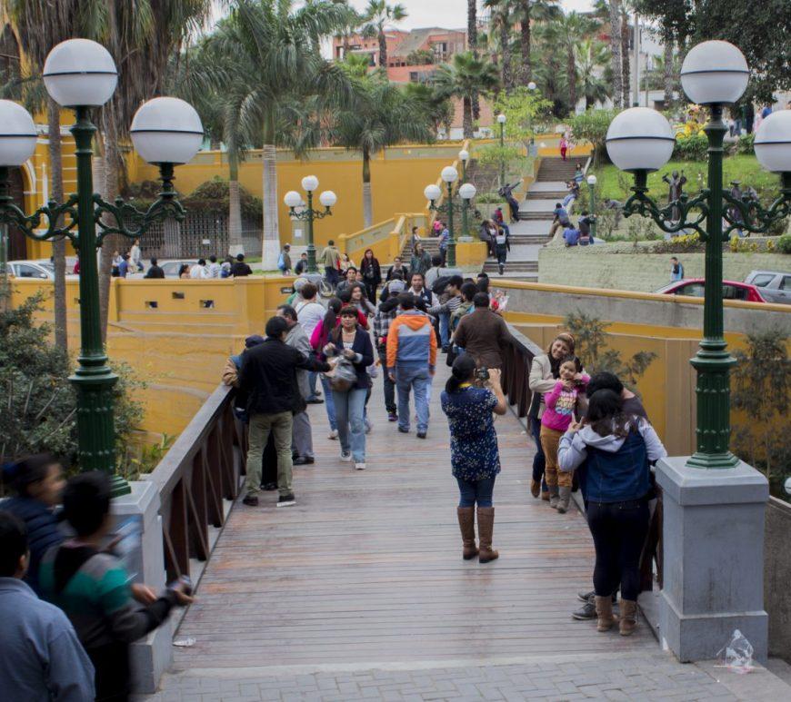 Varias personas contienen la respiración al cruzar el Puente de los Suspiros en Barranco (Lima).